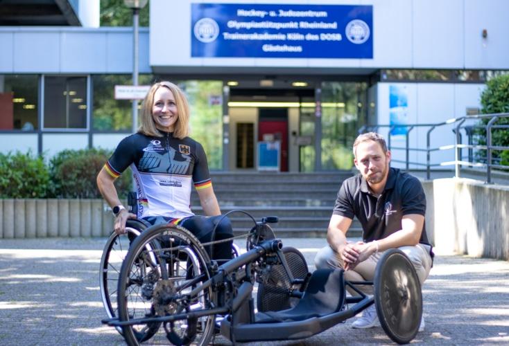 Para-Radsportlerin Annika Zeyen mit OSP-Leiter Daniel Müller vor der OSP-Zentrale in Köln (Bild: OSP NRW/Rheinland; Sebastian Meyer-Köring)